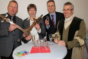 Ralf Flügge-Kranz und Frauke Kesper-Weinrich mit den Zeigern der alten Kirchturmuhr, Hartmut Büttner und Hartwig Möller in Tracht.